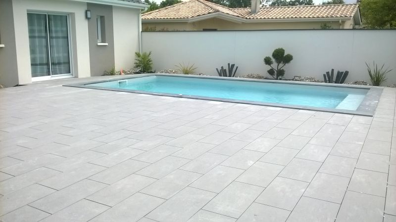 Piscine avec une terrasse en carrelage gris for Photo terrasse carrelage gris